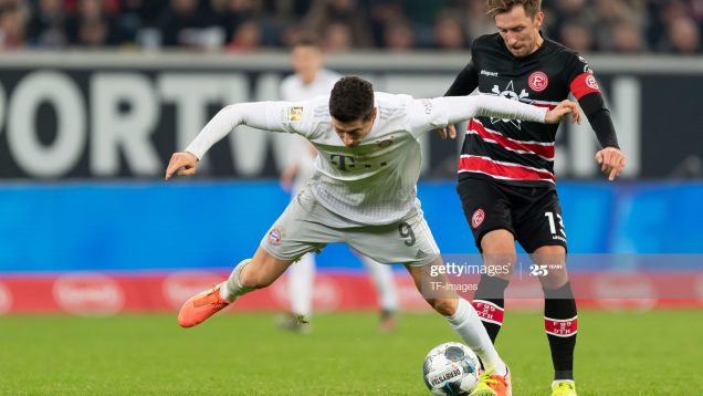 Robert Lewandowski of FC Bayern Muenchen and Adam Bodzek of Fortuna Duesseldorf